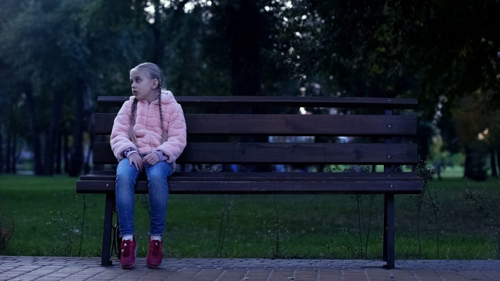Sad school girl sitting on bench in park, lost kid, waiting for parents