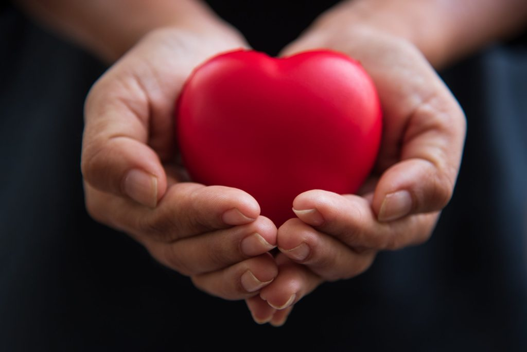 Close up hands giving red heart as sign of compassion and helping