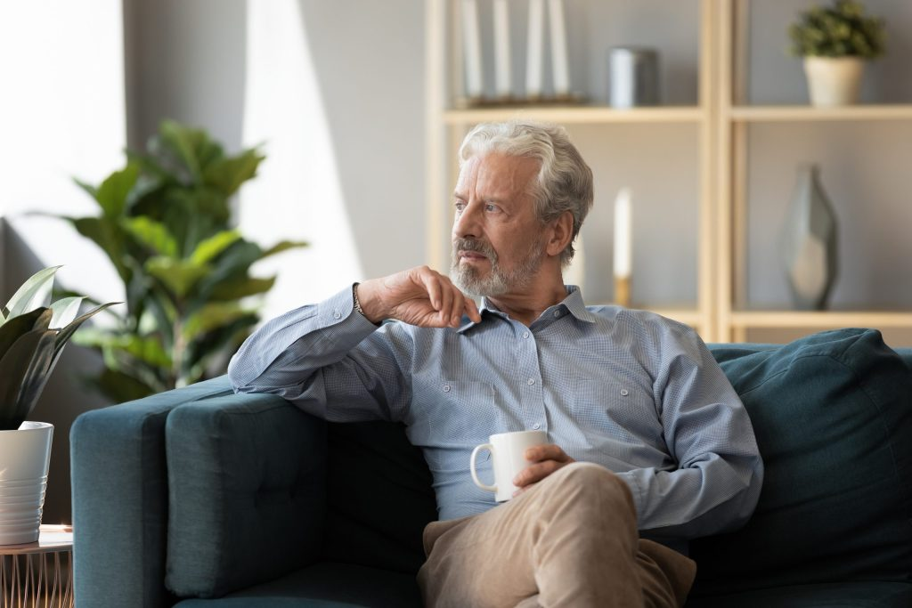 Thoughtful older man sitting on couch alone, feeling lonely