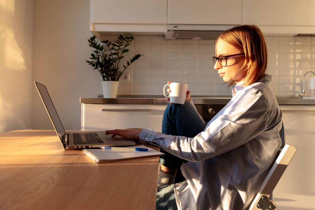 working from home in sunny room, holding coffee/tea mug. Cozy office workplace, remote working, stay home concept