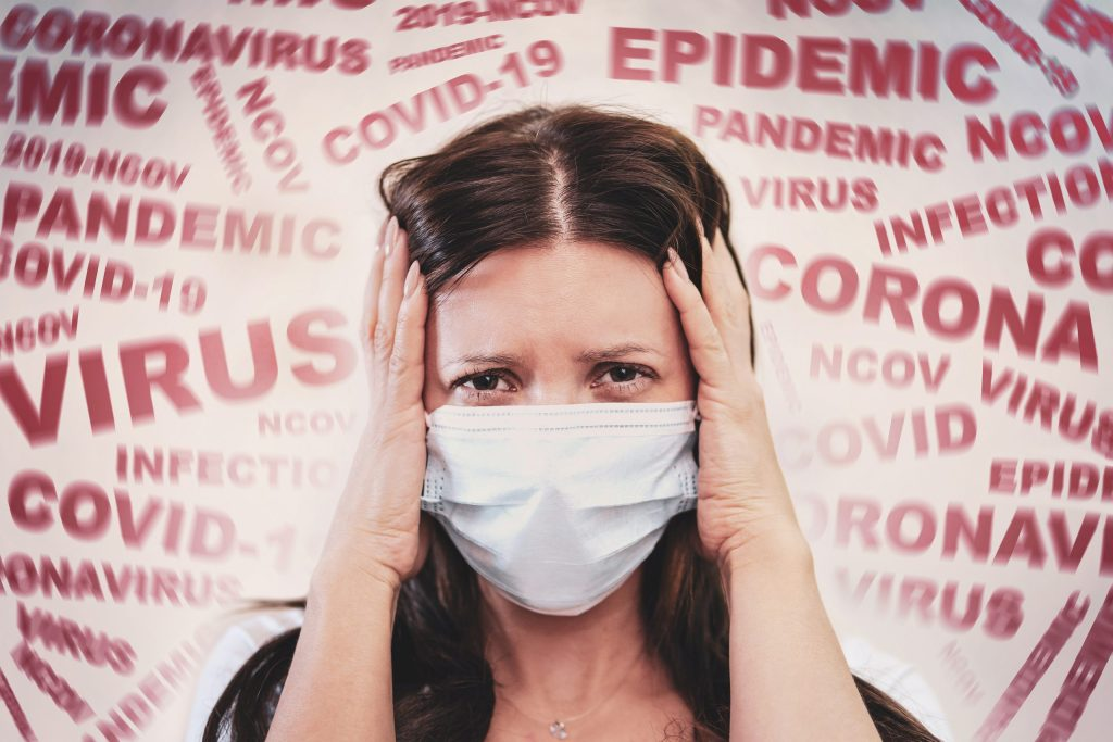 a woman with a mask on her face, scared by the news of the coronavirus covid-2019. Panic situation. Fear of getting sick.