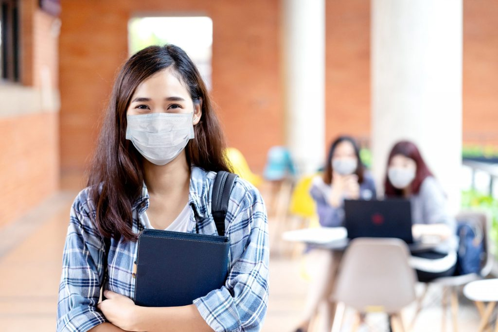 Student wearing mask holding notebook, school reopening and unlock after covid