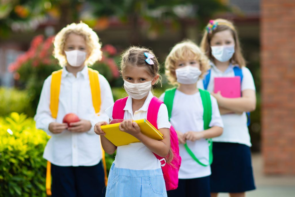 School children wearing face masks during corona virus and flu outbreak. Group of kids in masks for coronavirus prevention.