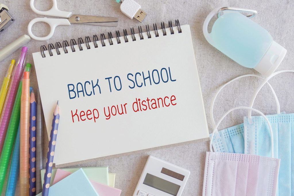 School stationery supplies, medical masks and hand gel sanitizer, keep your distance, school reopening, returning back to school for post covid-19 coronavirus pandemic, new normal concept