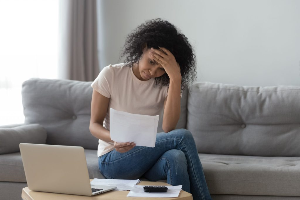 Stressed Black woman holding bills worried about bankruptcy bank debt
