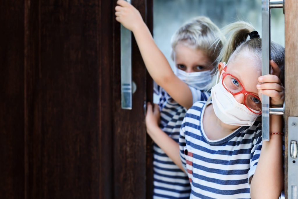 Little children looking unhappy and depressed after staying at home due banned street activity. Kids wearing medical face masks go out for outside walk, ending coronavirus Covid-19 disease quarantine.