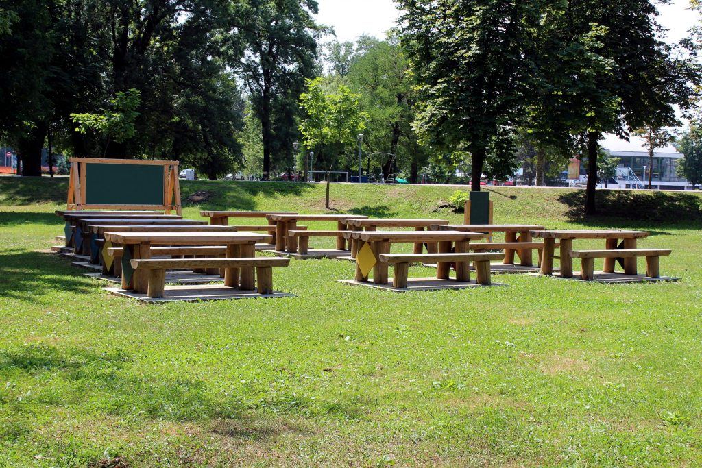 Outdoor classroom with blackboard tables and benches surrounded with grass and tall trees