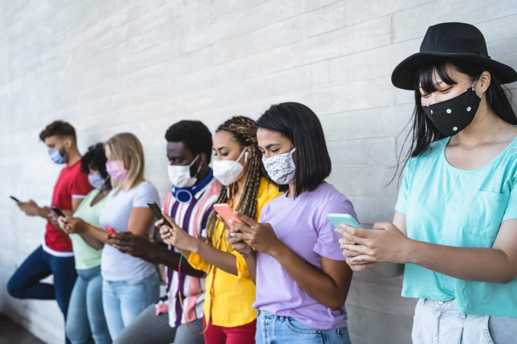 Young people wearing face mask using mobile smartphone outdoor - during corona virus outbreak