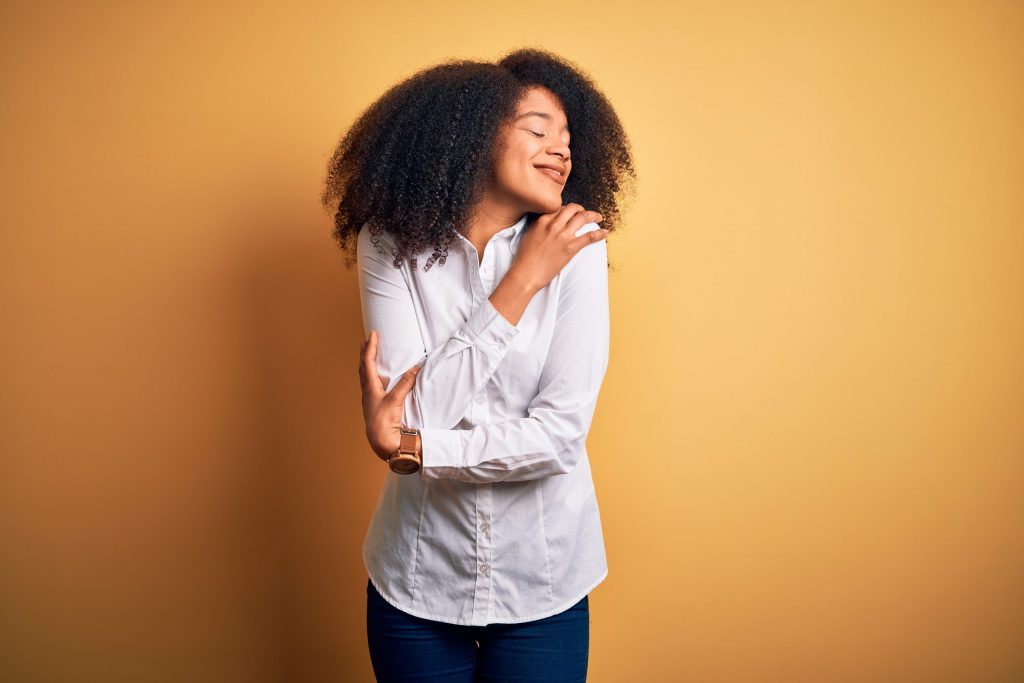 Young beautiful african american elegant woman with afro hair Hugging herself, happy and positive, smiling confident. Self love and self care