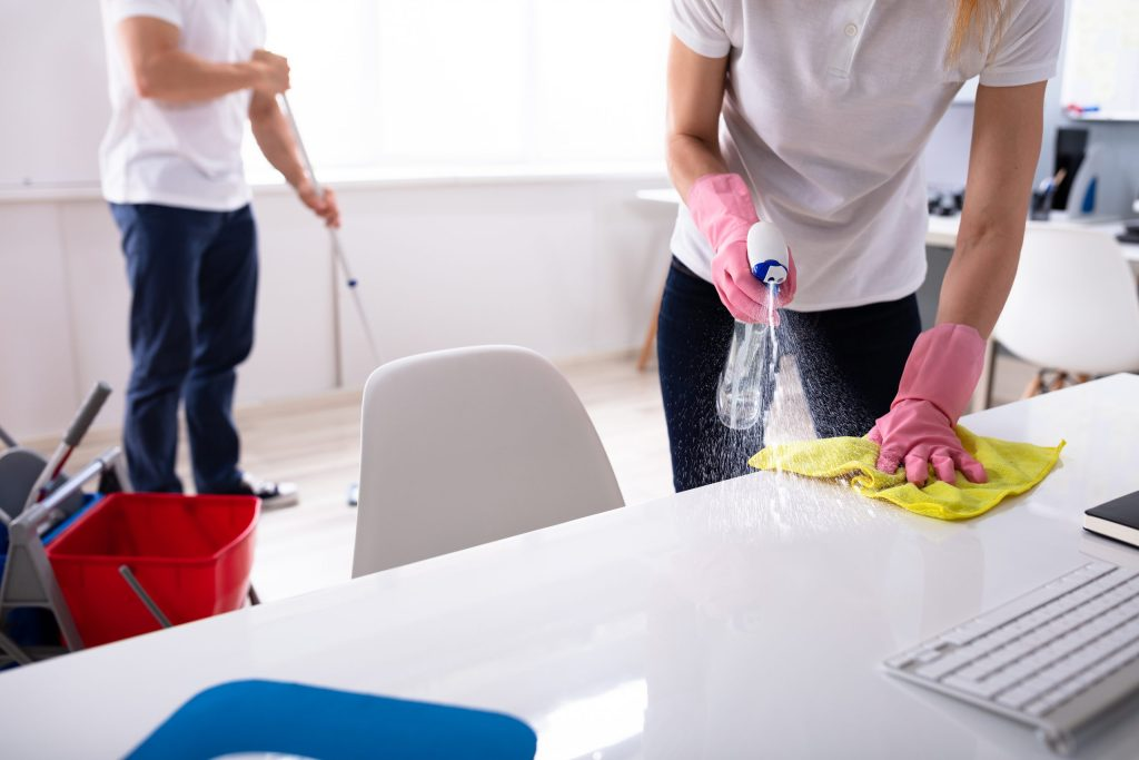 2 Janitors Cleaning Desk And Mopping Floor