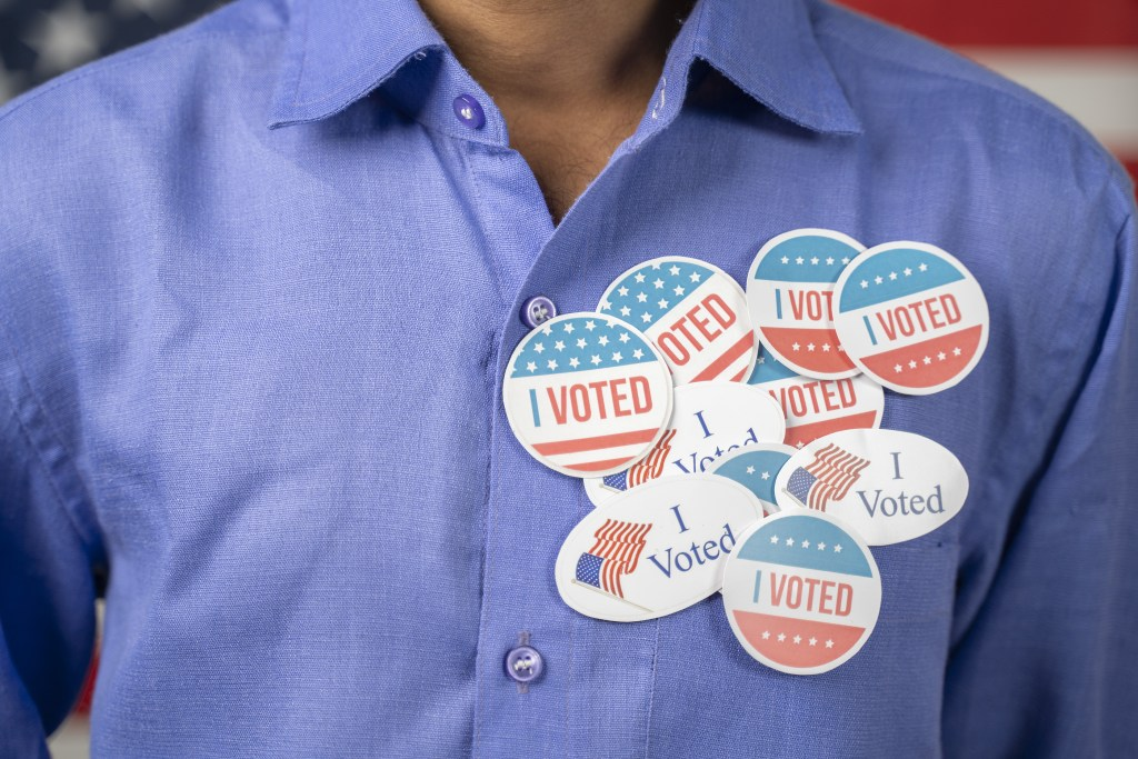 Close up of multiple I Voted stickers on blue shirt - Concept of US election voter fraud by placing multiple voting stickers.