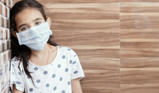 Concept of PTSD or post-traumatic stress disorder after covid-19 or coronavirus pandemic - Young teenager girl with medical mask wearing sat by leaning on well in sad, fear, or anxiety