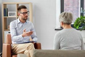 psychologist talking to senior woman patient at psychotherapy session