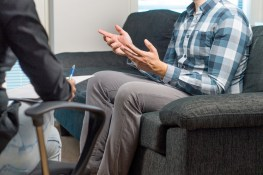 Man talking and waving hands in therapy session with psychiatrist/ psychologist.