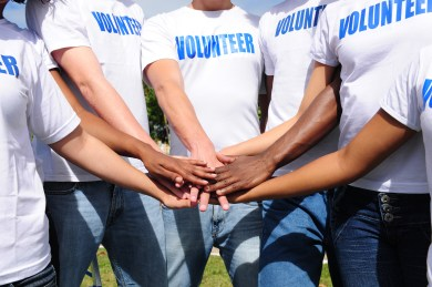 multi-ethnic volunteer group hands together showing unity