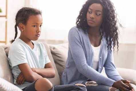black mother looking at her teen daughter to help her, sitting on couch at home