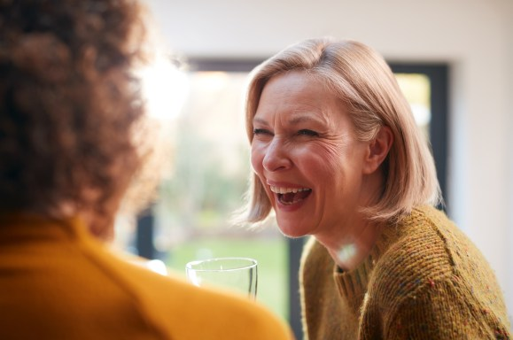 Two Mature Female Friends Meeting At Home To Talk And Drink Wine Together