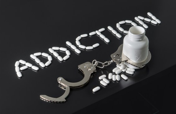 Addicted to drugs or free from addiction to medicine. Addiction written with pills. Medicine spilling out from a bottle locked with open handcuffs.