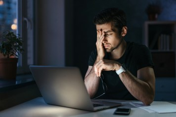 Young businessman has headache while working overtime with laptop at home office late night. Stressed depressed freelancer touching his head, feeling pain in eyes. Insomnia, internet addiction