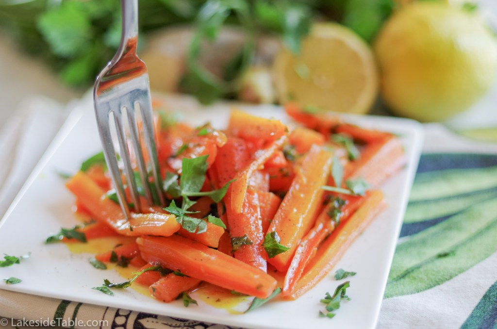 turmeric honey glazed carrot recipe - plate of carrots cut into long match sticks, sprinkled with parsley with a fork coming down into them. Behind this is an array of fresh parsley and lemons.