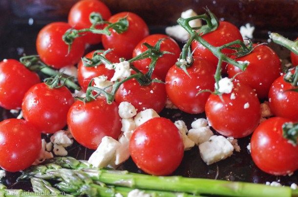 Clusters of bright red cherry tomatoes with the stems. Feta scattered around them with the braised asparagus