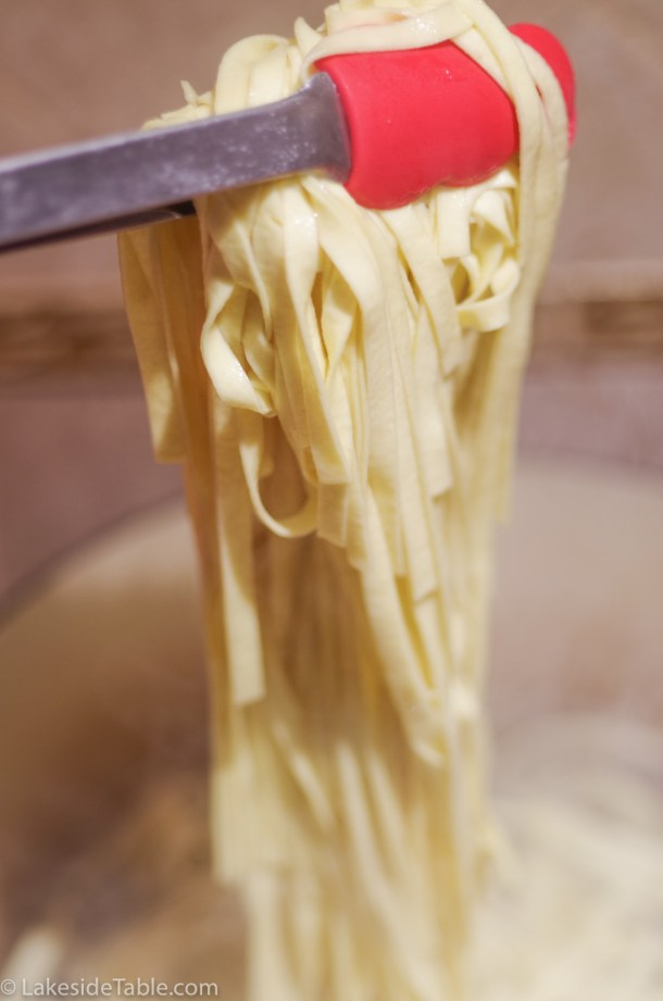 pulling fresh pasta out of the water with red tongs