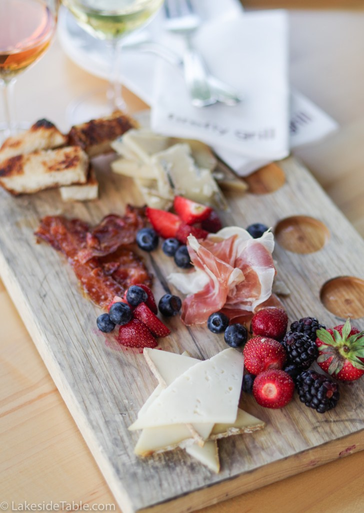 Charcuterie board of blue cheese, swiss cheese, fruit, bacon, and ham on a Firefly Grill wooden board