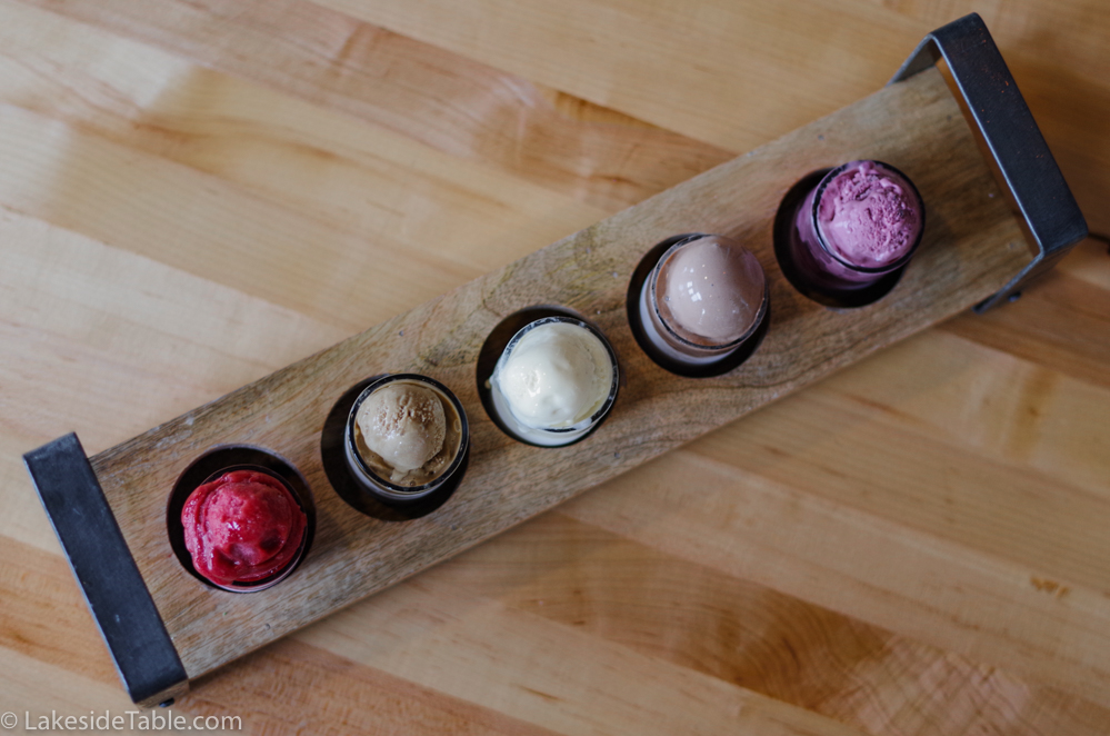 top down view of 5 ice cream flavors lined up in separate cups on a board on a wooden table