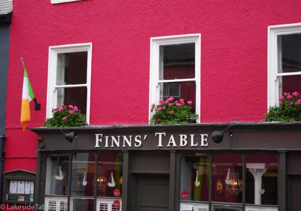 the front of Finns' Table restaurant is hot pink with flower boxes full of pink geraniums in the windows above the door.