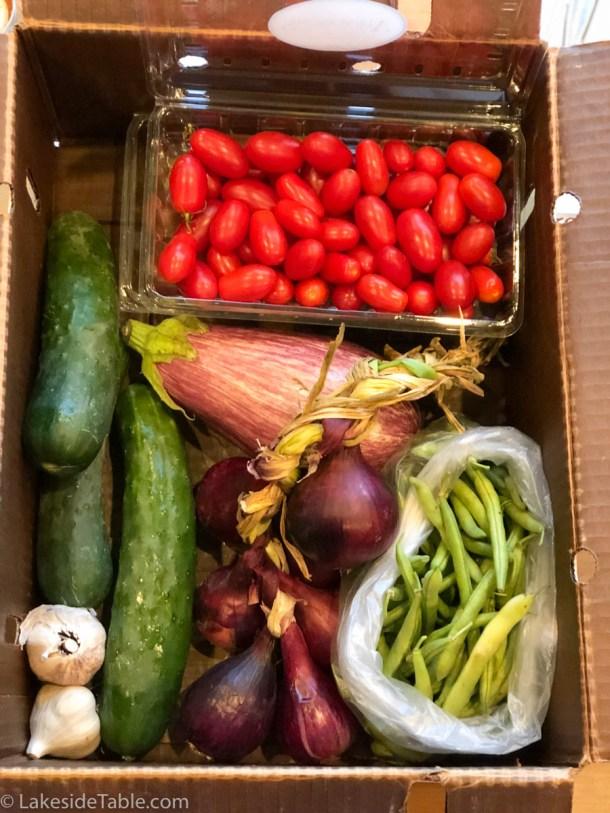 Box full of organic produce: cherry tomatoes, cucumbers, eggplant, garlic, beans and onions