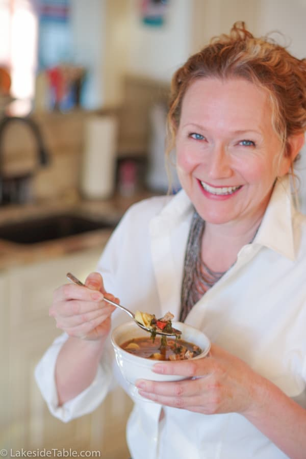 Madalaine holding a bowl of easy tortellini soup in her kitchen