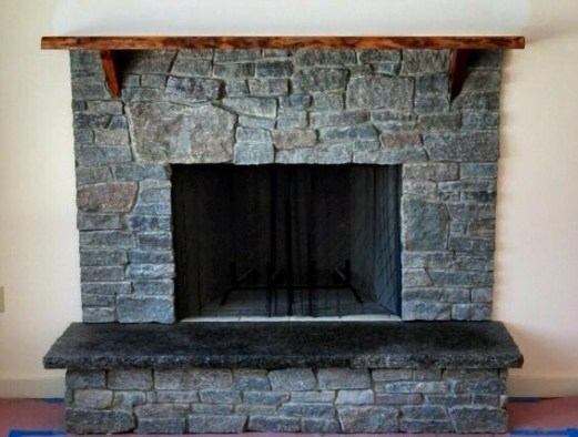 Dark ledge stone with rustic mantel