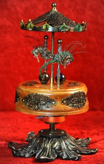 Two Pacific Giant Seahorses, peacock feathers, genuine pink garnets set in 14k gold, antique marbles. Movement: Wind up music box. The two seahorses move forward and upwards and then downwards and backwards. 12 x 9 in. in diameter, $1,500.00