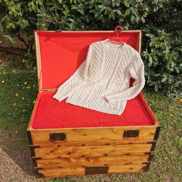 Pull irlandais en coton présenté sur une malle ancienne restaurée. La Malle au Coton