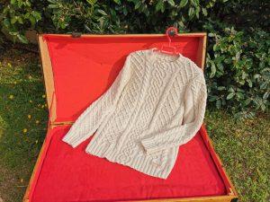 Pull irlandais traditionnel en coton présenté sur une malle ancienne restaurée. La Malle au Coton