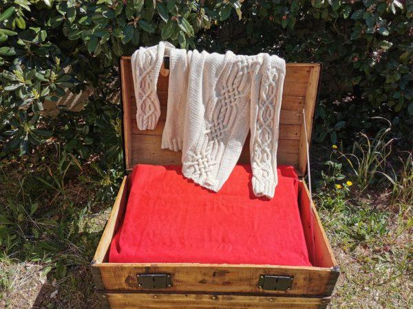 Pull d'Aran asymétrique en coton bio posé sur malle ancienne