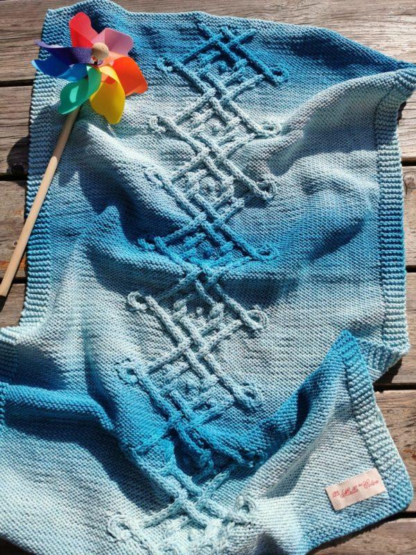 Couverture bébé bleu lagon dégradé vue dans son ensemble sur une table au soleil avec un petit moulin à vent.