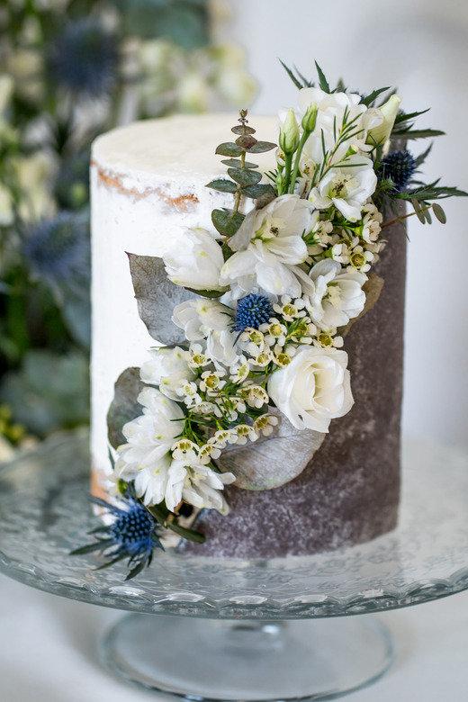 joli wedding cake fleuri blanc et gris avec des touches de bleu