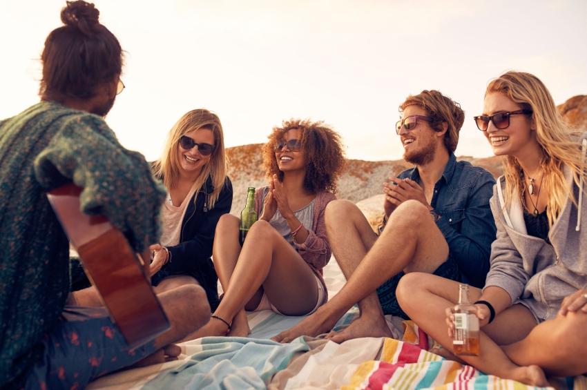 cinq-amis-sur-une-plage-qui-boivent-des-bieres-en-jouant-de-la-musique
