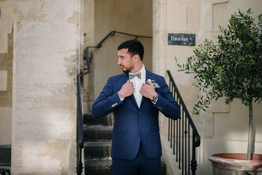 marié en costume bleu marine et noeud papillon