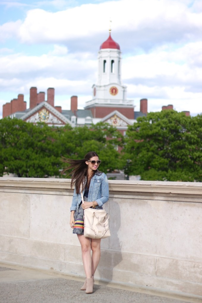 Casual Denim & High-waisted Skirt  with booties and nude tote on the Charles River in front of Harvard University