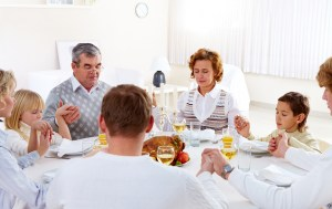Portrait of big family sitting at festive table and holding each