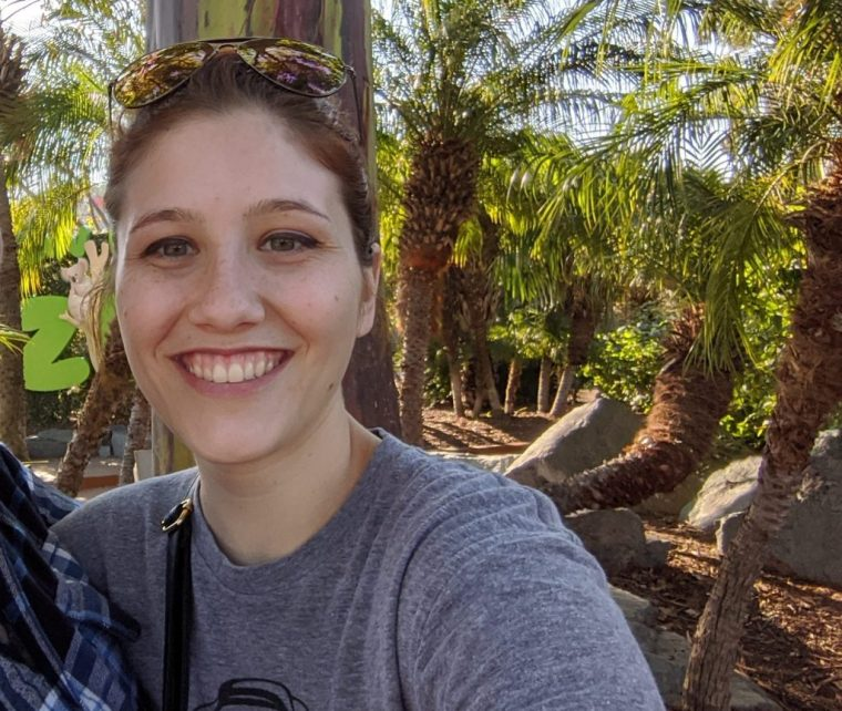Image of a person standing in an outdoor setting, possibly in front of the San Diego Zoo sign.  The person is smiling big at the camera.