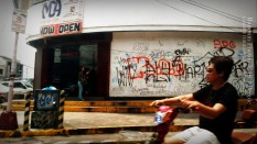 Graffiti. A man on a motorcycle drives by a establishment that has a wall covered by writings.