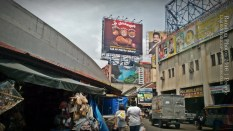 Billboards. Signages block the skyline in populated areas in Manila such as this one. The women at the center carry plastic bags of goods as they walk past a store. Lines of store, such as the souvenir store on the left, can be found underneath elevated roads.