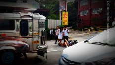 Motorcycle accident. A man cries in pain as bystanders witness an accident at a busy section in Pampanga.