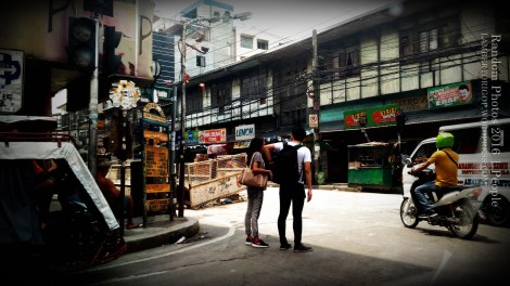 A young couple under a building's shadow. A young couple stops before a crossing.