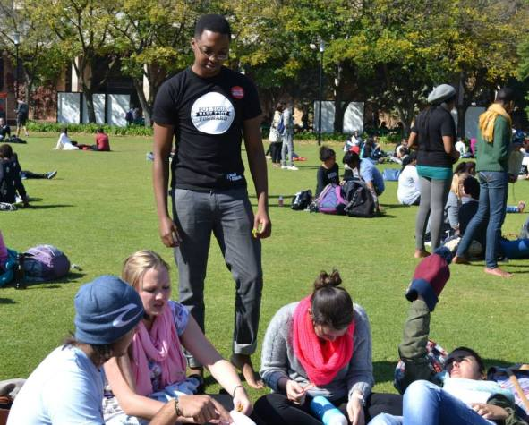 Wayne Mahlanga hands out stickers to promote the event. Photo: Lameez Omarjee