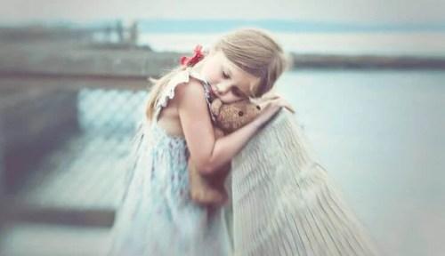 cicatrici bambina sul ponte abbraccia orsacchiotto di pezza