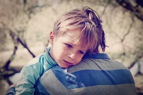 Bambino triste abbracciato a suo padre